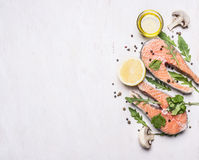 Two salmon steak, butter, pepper and salt, lemon, herbs border ,place for text  wooden rustic background top view Royalty Free Stock Photo
