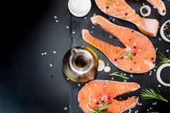 salmon steak, pepper and salt, herbs on black stone concrete table, copy space top view royalty free stock photography