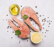 Two salmon steak, butter, pepper and salt, lemon, herbs on wooden rustic background top view close up Stock Photos