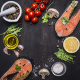 Two salmon steak, butter, salt and pepper, lemon and cherry tomatoes, garlic, herbs place for text,frame on wooden rustic backgrou Royalty Free Stock Photos