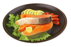 Two salmon steak on dark dish Royalty Free Stock Images