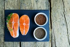 Two salmon steaks lie on a black board, and alongside there are vitamins and seeds of chia and flax. Top view. The choice to get v. Itamins Stock Photo