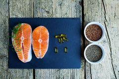 Two salmon steaks lie on a black board, and alongside there are vitamins and seeds of chia and flax. Top view. The choice to get v. Itamins Stock Photos