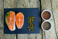 Two salmon steaks lie on a black board, and alongside there are vitamins and seeds of chia and flax. Top view. The choice to get v. Itamins Royalty Free Stock Images