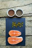 Two salmon steaks lie on a black board, and alongside there are vitamins and seeds of chia and flax. Top view. The choice to get v. Itamins Royalty Free Stock Image
