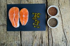 Two salmon steaks lie on a black board, and alongside there are vitamins and seeds of chia and flax. Top view. The choice to get v. Itamins Stock Images