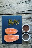 Two salmon steaks lie on a black board, and alongside there are vitamins and seeds of chia and flax. Top view. The choice to get v. Itamins Stock Image