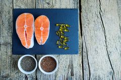 Two salmon steaks lie on a black board, and alongside there are vitamins and seeds of chia and flax. Top view. The choice to get v. Itamins Royalty Free Stock Photos