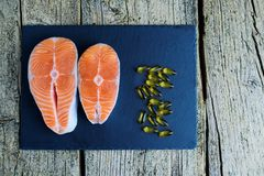 Two salmon steaks lie on a black board, and alongside there are vitamins. Top view. The choice to get vitamins.  Royalty Free Stock Photography
