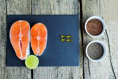 Two salmon steaks lie on a black board with a piece of lime, and alongside there are vitamins and seeds of chia and flax. Top view. Two salmon steaks lie on a Royalty Free Stock Photography