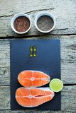 Two salmon steaks lie on a black board with a piece of lime, and alongside there are vitamins and seeds of chia and flax. Top view. Two salmon steaks lie on a Stock Photos