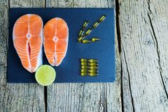 Two salmon steaks lie on a black board with a piece of lime, and alongside there are vitamins. Top view. The choice to get vitamin. S Royalty Free Stock Photos