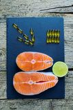 Two salmon steaks lie on a black board with a piece of lime, and alongside there are vitamins. Top view. The choice to get vitamin. S Royalty Free Stock Images