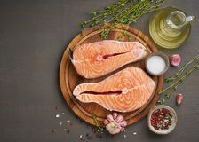 Two salmon steaks, top view, copy space. Fish fillet, large sliced portions  on chopping board on a dark table. Two salmon steaks, top view, copy space. Fish royalty free stock photography