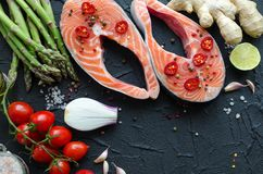 Two salmon steaks with vegetables and spices royalty free stock image