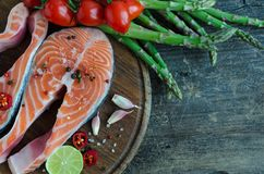 Two salmon steaks with vegetables and spices. Two frash raw salmon steaks with vegetables and spices: asparagus, garlic, tomatoes, pepper corns, salt, chili and Royalty Free Stock Photo