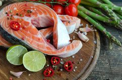 Two salmon steaks with vegetables and spices. Two frash raw salmon steaks with vegetables and spices: asparagus, garlic, tomatoes, pepper corns, salt, chili and Royalty Free Stock Photos