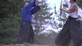 Two samurai masterfully fight in the woods stock footage