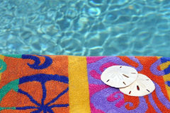 Two sand dollars against beach towel and water Royalty Free Stock Photography