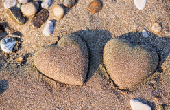 Two sand heart shape in the sand by the sea Royalty Free Stock Images