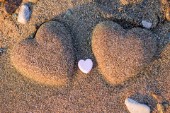 Two sand heart shape in the sand by the sea Royalty Free Stock Photos