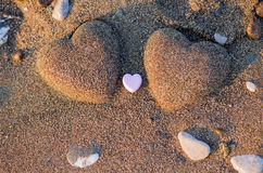 Two sand heart shape in the sand by the sea Stock Photo