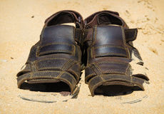 Two sandals to sprinkle with sands. Heat summer background Stock Photo