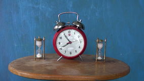 Two sandglass and vintage alarm-clock stock video footage