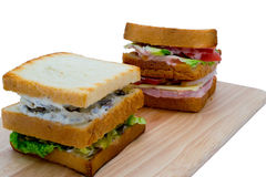 Two sandwiches. On a chopping board on white background royalty free stock images