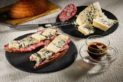 Two sandwiches from black bread with cheese of Dorblu and raw smoked sausage on black slate plates, a cheese knife, a. Two sandwiches from black bread with Stock Photo