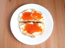 Sandwiches with butter and red caviar on white bread lies on white round plate on wooden background Stock Photography