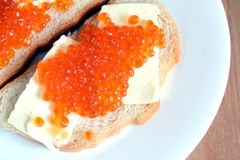 Sandwiches with butter and red caviar on white bread lies on white round plate on wooden background Stock Images