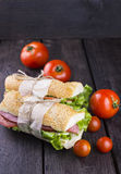 Two sandwiches on a dark wooden background and tomatoes.  Royalty Free Stock Photos