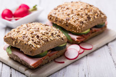 Two sandwiches with ham, radishes and cucumber. Two sandwiches with ham, radishes and gherkin on wooden board Royalty Free Stock Photos
