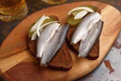 Sandwiches with smelt fish and beer. Two sandwiches with salt smelt fish, pickles, onion, and two glasses of beer Royalty Free Stock Photography