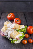 Two sandwiches which are tied up by a cord on a dark wooden back. Ground and tomatoes Stock Photos