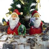 Two santa claus figurine and mini christmas trees royalty free stock photo