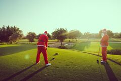 Two Santa Claus jumping on the golf course.