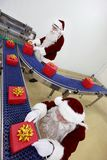 Two santa clauses working at production line royalty free stock photo
