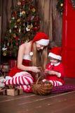 Two Santa girls decorating Christmas tree having fun. New year interior. Xmas atmosphere, family celebrating holidays. Stock Photo