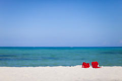 Two santa hats on beach Stock Photo