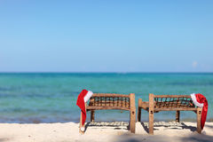 Two santa hats on sunbeds Royalty Free Stock Images