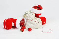 Two Santa shoes with red mat christmas balls and Santa bag with stack of money Stock Images