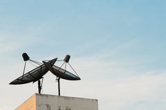 Two satellite dishes during sunset with copy space on blue sky background Royalty Free Stock Photo