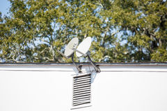 Two Satellite Dishes on White Building Royalty Free Stock Image