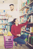 Two satisfied adult people in good spirits selecting detergents. оn the shelves in the store Royalty Free Stock Photos