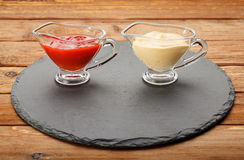 Two sauceboats with condiments. Closeup of pair glass sauce-boats with  ketchup and mustard on black round slate plate Royalty Free Stock Photo