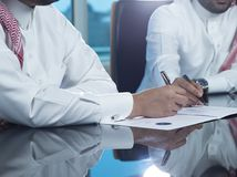 Two Saudi Businessmen Hands Signing A Ducument. Two Saudi Businessmen Hands Signing a document, contract or making a deal Royalty Free Stock Image