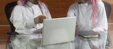 Two Saudi Businessmen Working on a Laptop. Two Saudi Businessmen Meeting, Working on a Laptop Stock Photo
