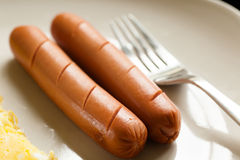 Two sausages on the white plate. Selective focus, close-up Royalty Free Stock Image